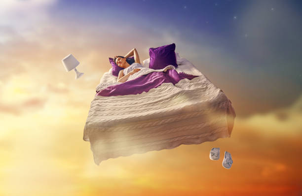 girl is flying in her bed Woman's dreams. Pretty girl is flying in her bed trough star sky. dreamlike stock pictures, royalty-free photos & images