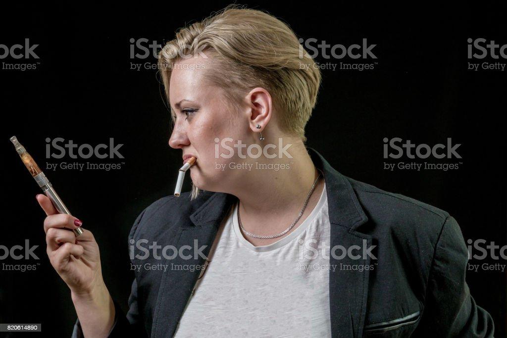 Girl is hesitating to vaping vaporizer stock photo