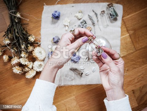 A girl is holding a little glass jar  on her altar in lavender tones. You can see dried flowers and crystal jars.