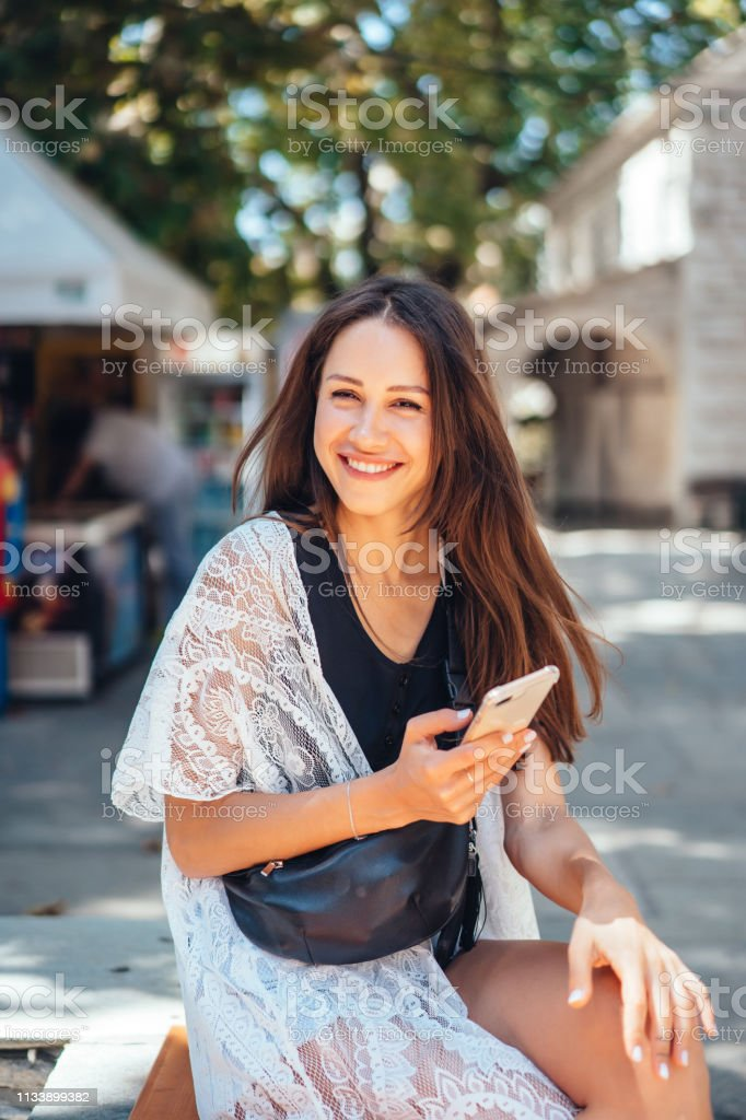 A girl is holding a phone and posing on the camera. The Internet. Message. stock photo