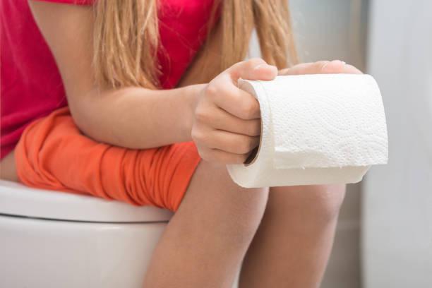 Uma garota está segurando um rolo de papel higiênico nas mãos dela, sentado na sanita - foto de acervo