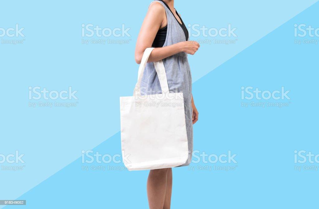 Mädchen hält Tasche Canvas Stoff für Mock-up leeren Vorlage auf blauem Hintergrund isoliert. – Foto
