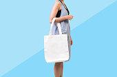 女の子は、青の背景に分離されたモックアップ空白テンプレートのバッグ キャンバス生地を保持しています。