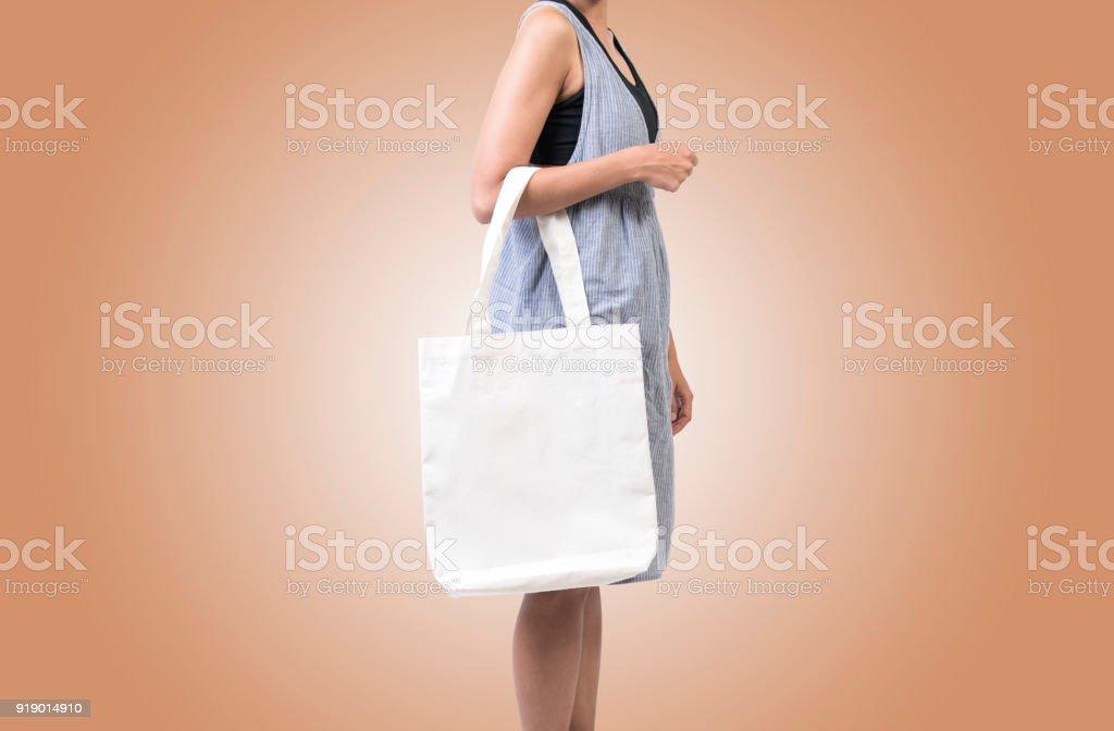 Mädchen hält Tasche Canvas Stoff für Mock-up leeren Vorlage auf farbigem Hintergrund isoliert. – Foto