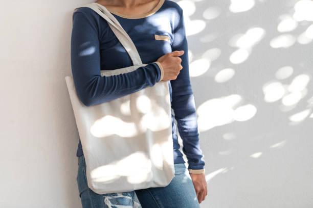 Mädchen hält Tasche Leinwand Stoff für Mockup leere Vorlage auf Sonnenlicht Hintergrund.  Konzept der globalen Erwärmung. – Foto