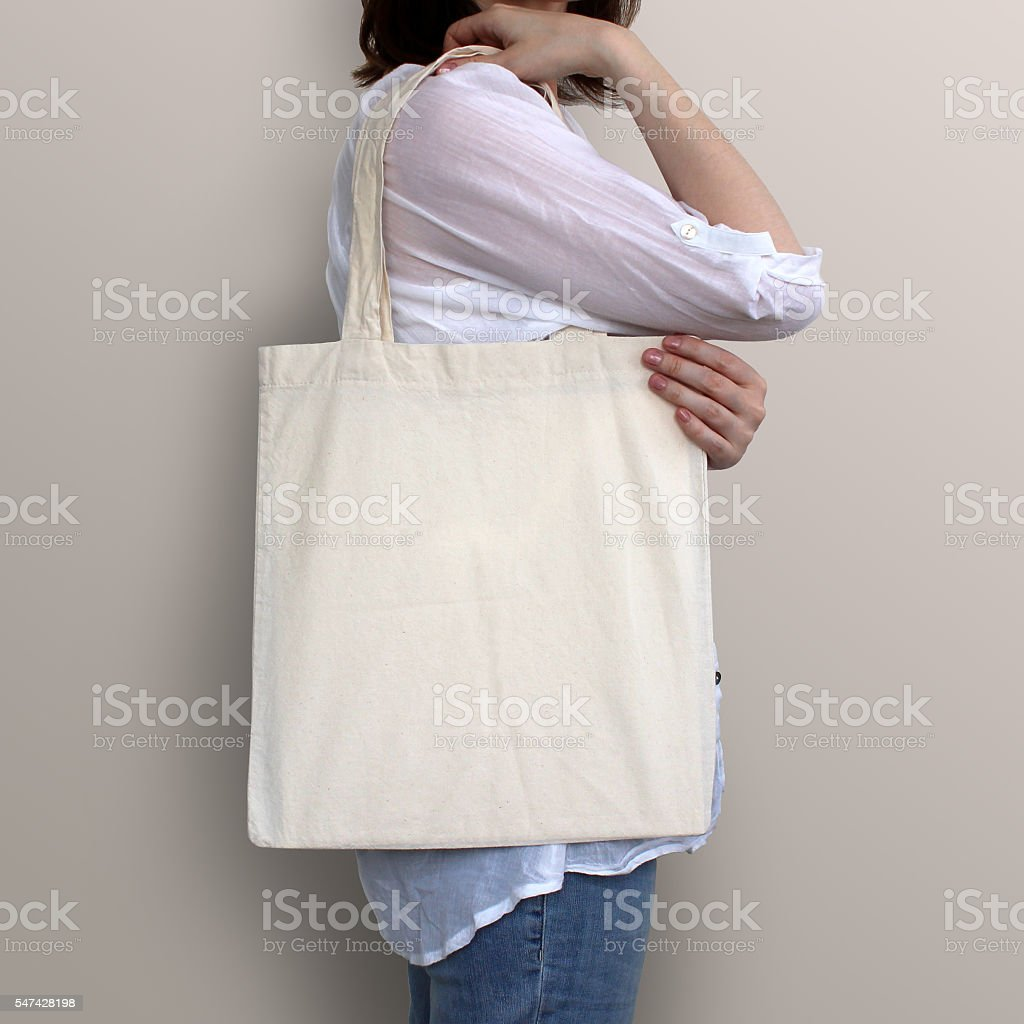 Girl is holding blank cotton eco bag, design mockup. stock photo