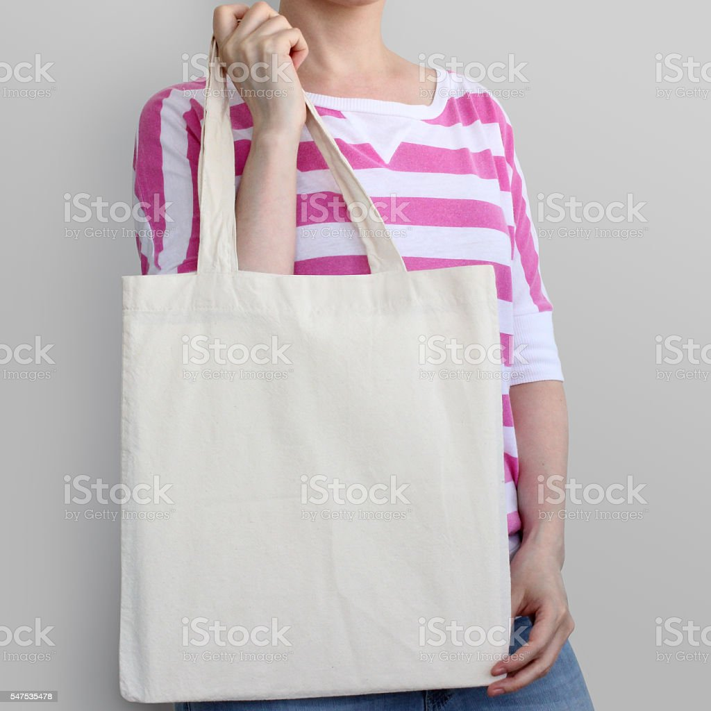 Girl is holding blank cotton eco bag, design mockup. - foto de stock