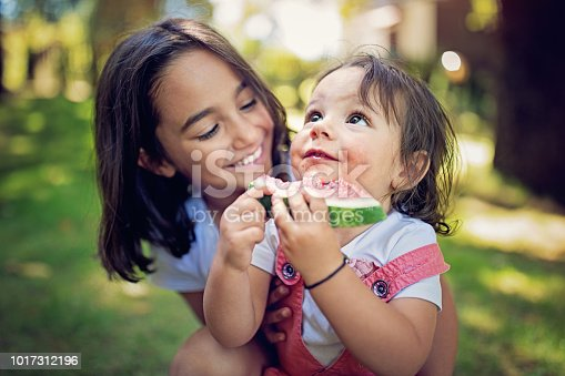 Girl is hugging her baby sister who is eating water melon