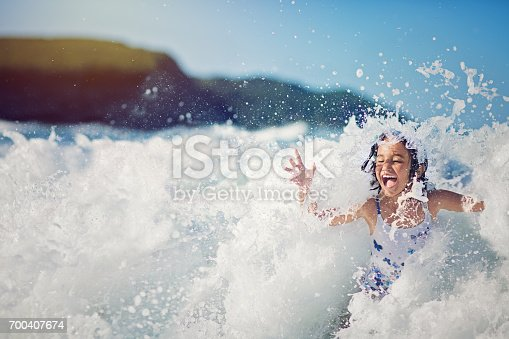 istock Girl is jumping and playing in the ocean in the big waves 700407674