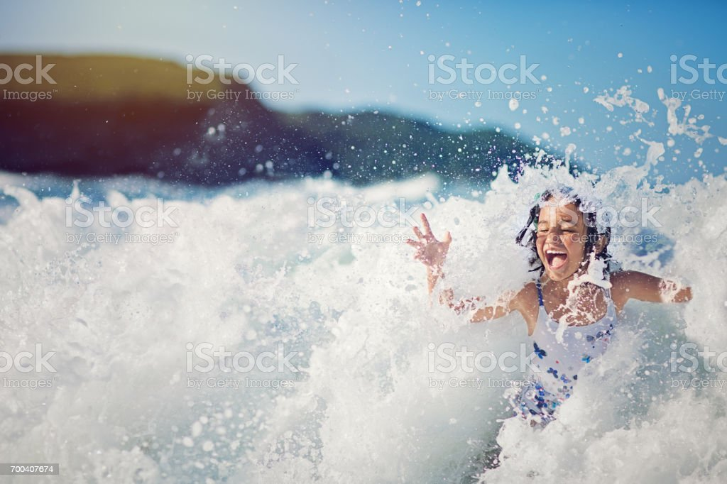 Girl is jumping and playing in the ocean in the big waves stock photo