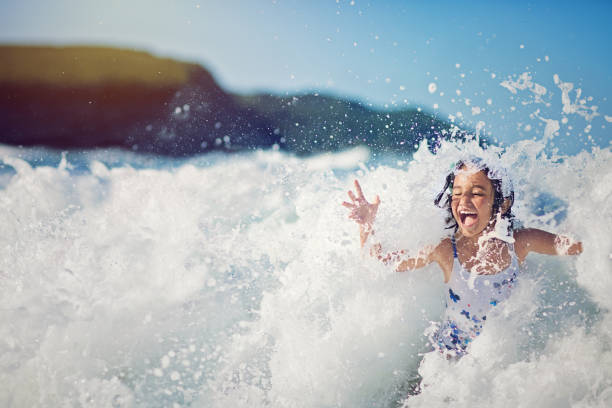 Girl is jumping and playing in the ocean in the big waves - foto stock