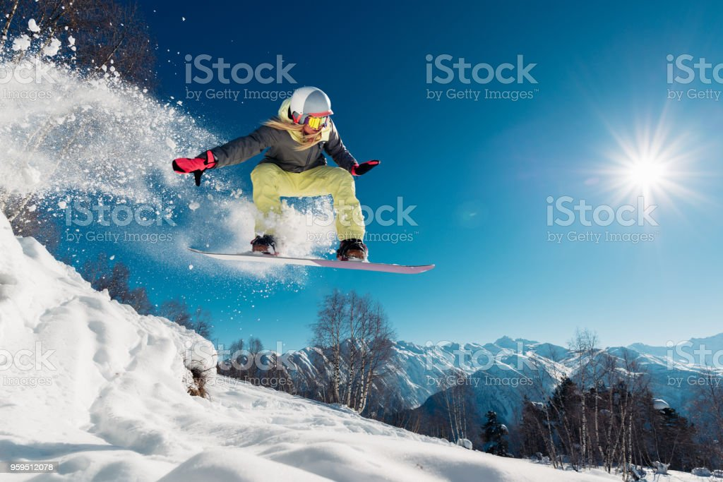 Girl is jumping with snowboard stock photo