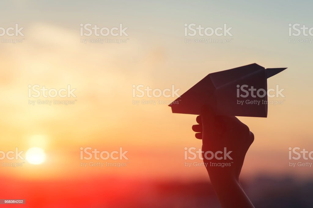 A girl is launching a paper airplane from a window at sunset. Support of the Telegram application and freedom internet. stock photo