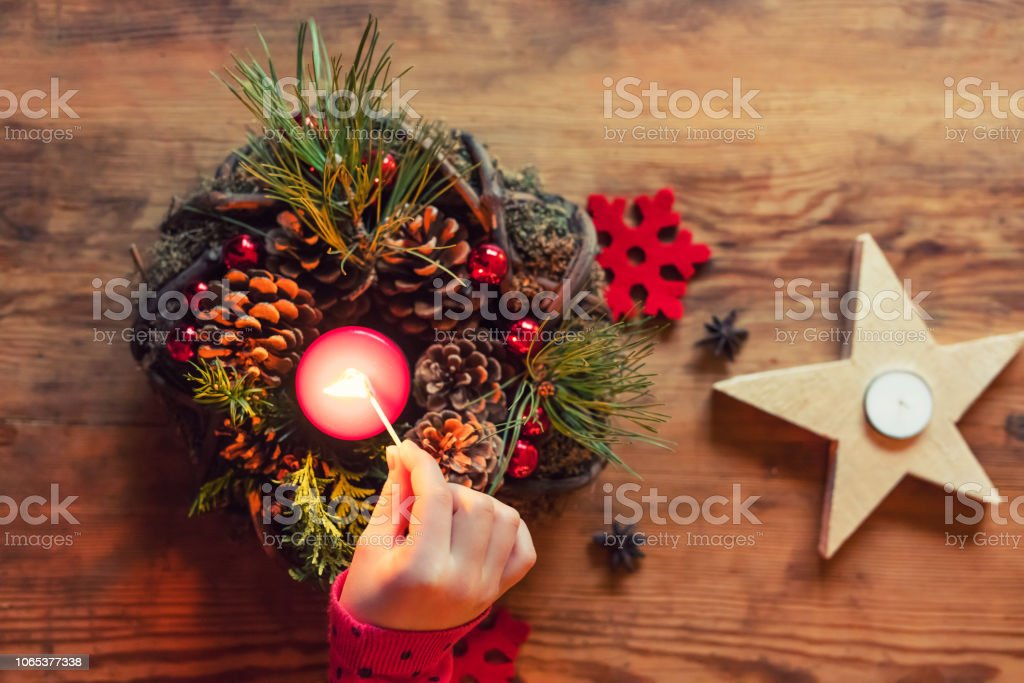 Girl is lighting candles on Advent wreath – High angle view