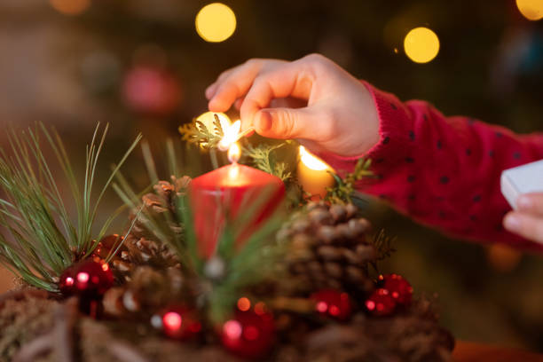 Girl is lighting candles on Advent wreath stock photo