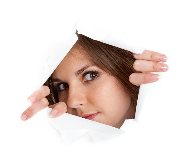 Girl is looking through a hole stock photo