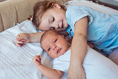 istock Girl is lying in bed with her newborn sister 1224410550