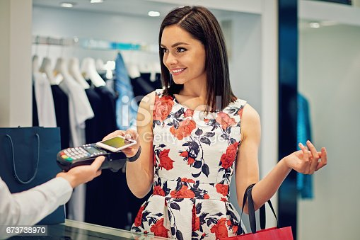 istock Girl is paying using her mobile phone in the Mall 673738970