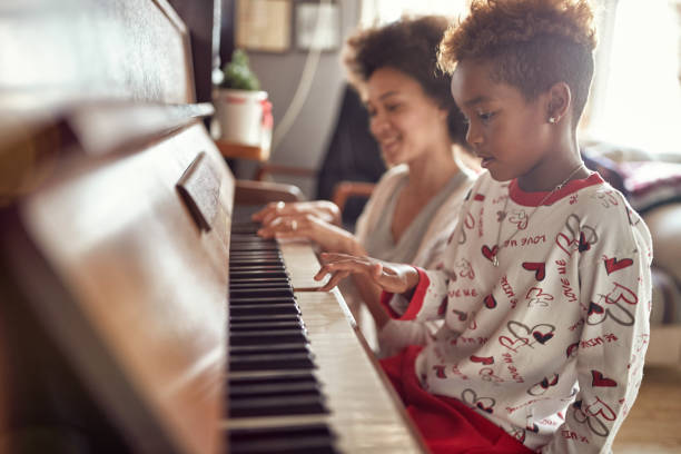 girl is playing on piano x-mas music. Concept Christmas, New Year, holiday, family happiness, childhood. stock photo