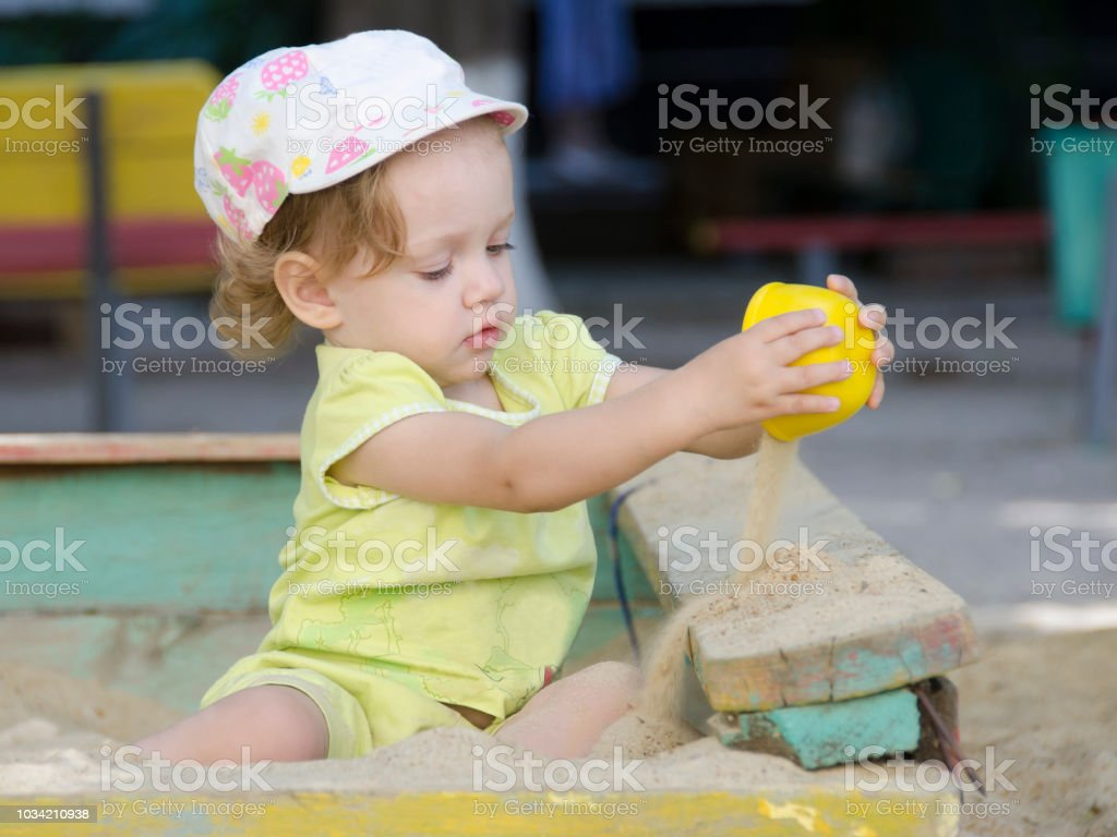 A girl is pouring sand in a sandbox stock photo
