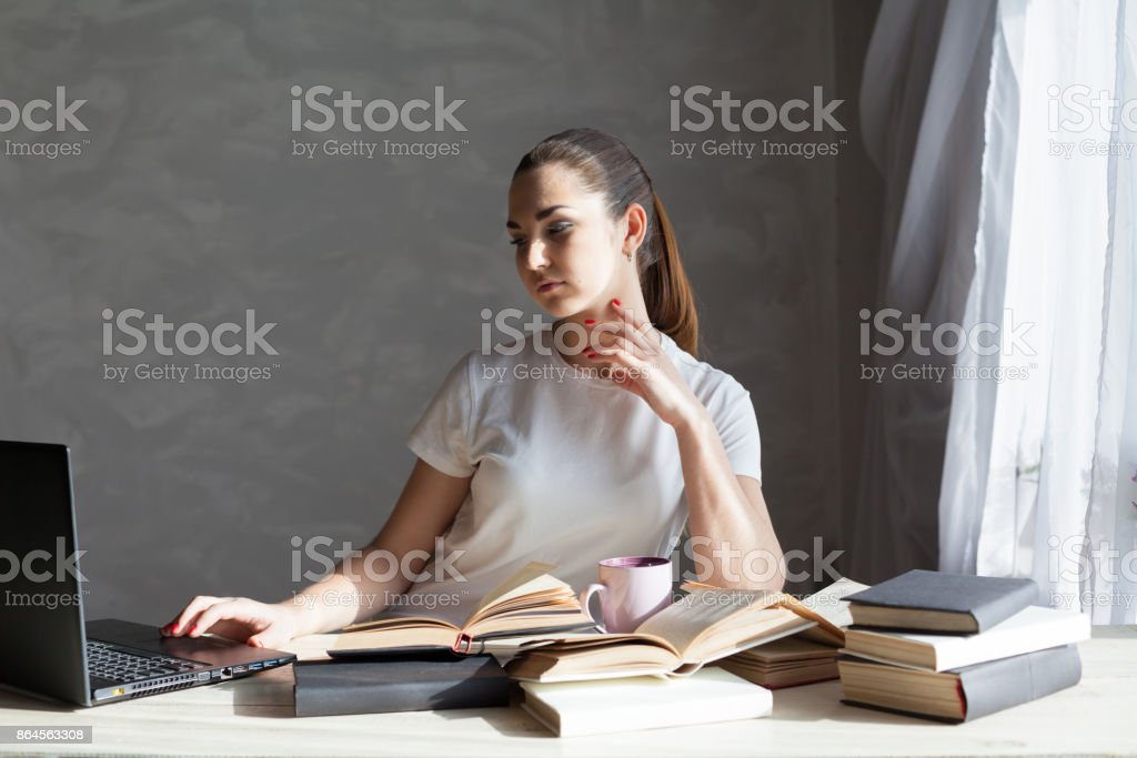 girl is preparing for the exam reading book works at the computer stock photo