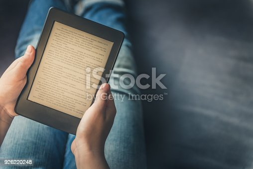 Girl is reading ebook on digital tablet device while relaxing on the sofa