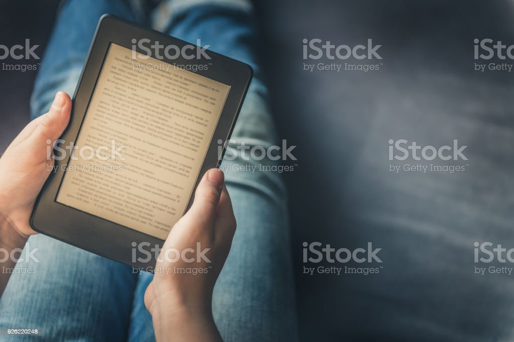 Girl is reading ebook while relaxing on the sofa stock photo