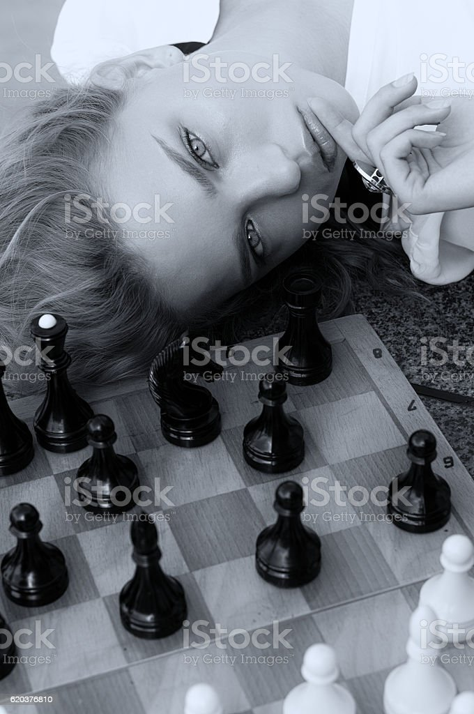 Girl is resting her head on a chess board zbiór zdjęć royalty-free