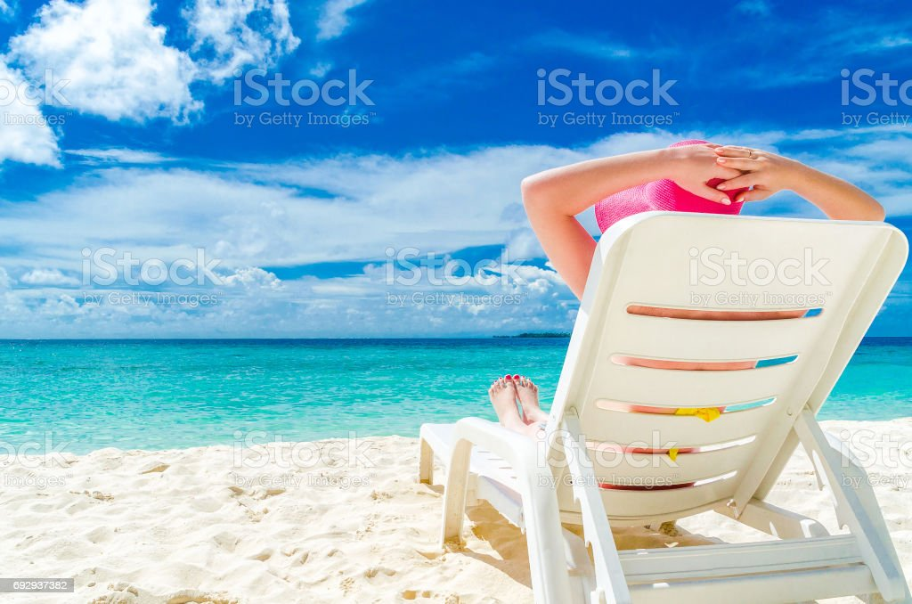 girl is resting on a deckchair in a pink hat stock photo