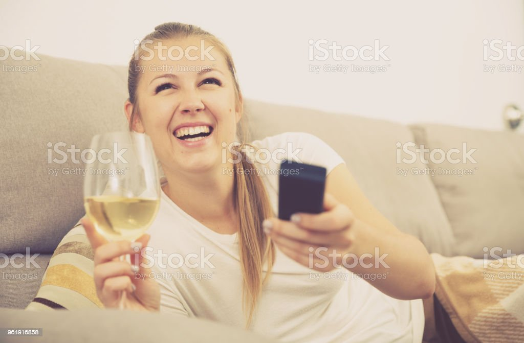 Girl is resting with wine and watching TV royalty-free stock photo