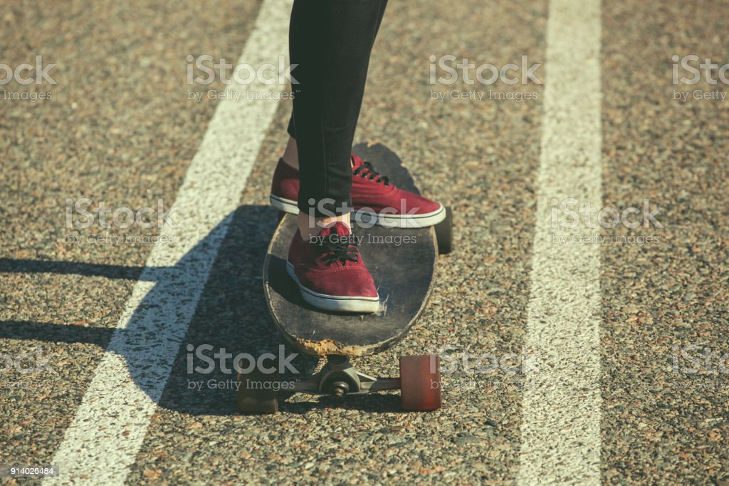 A girl is riding a longboard on the asphalt, legs close-up. stock photo