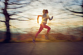 Girl is runing in the forest at the front of beautiful sunset