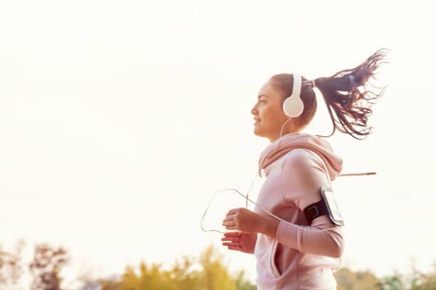 mädchen ist runing auf die stadt und die musik hören - motivationsmusik stock-fotos und bilder