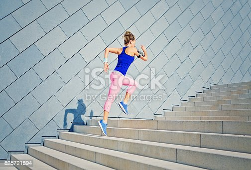 istock Girl is runing on the city stairs and listening the music 825721894