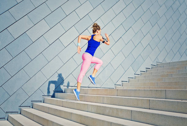 girl is runing on the city stairs and listening the music - vitality stock photos and pictures