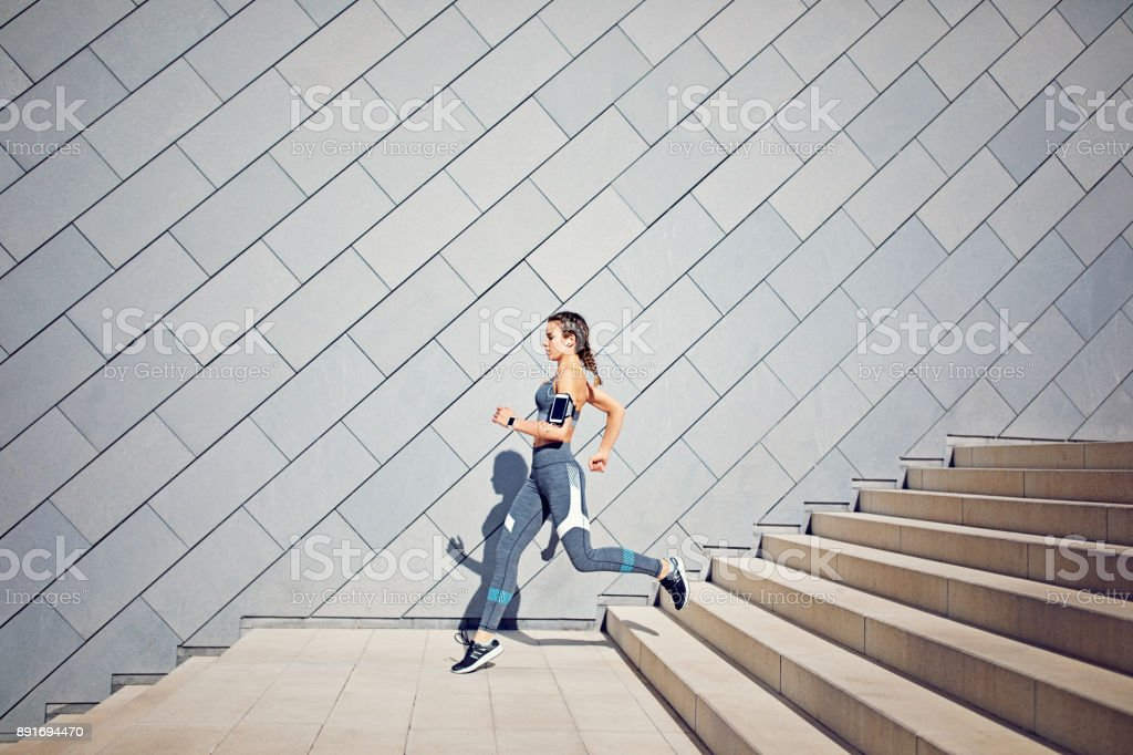 Girl is runing on the city stairs and listening the music stock photo