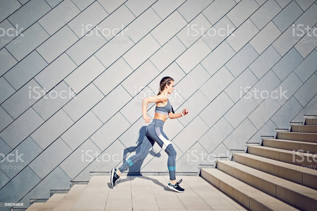 Girl is running on the city stairs and listening the music stock photo
