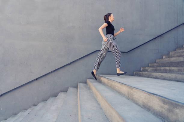 Mädchen läuft auf der Treppe der Stadt vor einer Betonwand – Foto