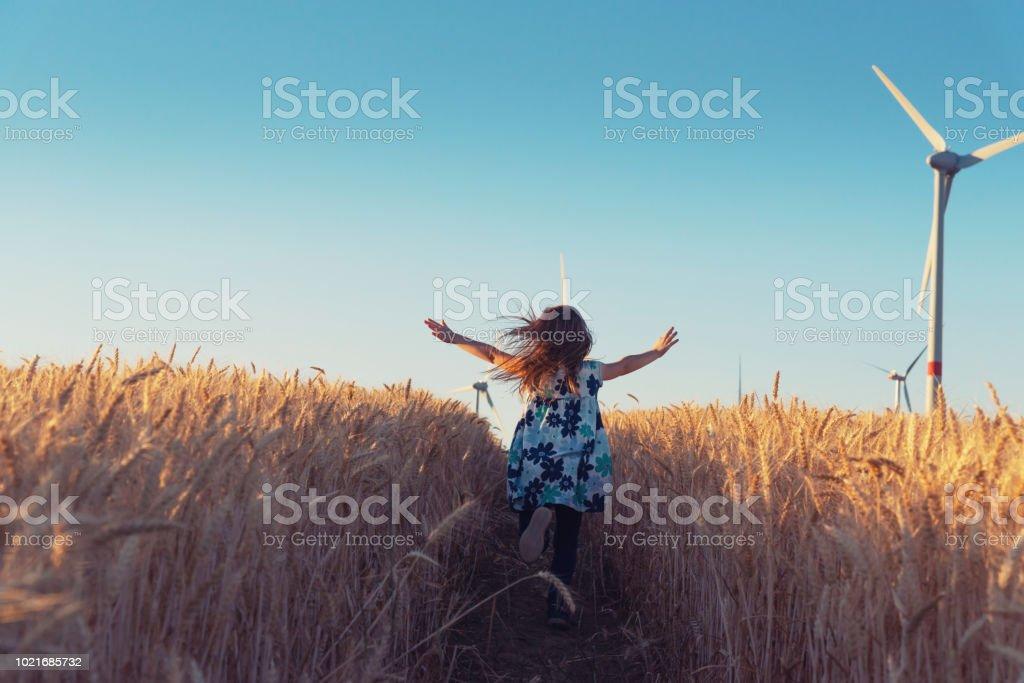 Mädchen läuft den Weg, um Windenergie – Foto
