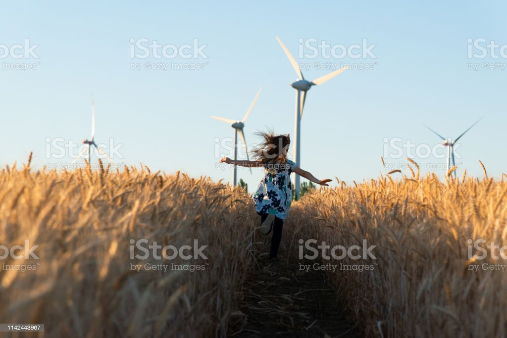 Girl is running the way to wind energy Girl is running the way to wind energy 6-7 Years Stock Photo