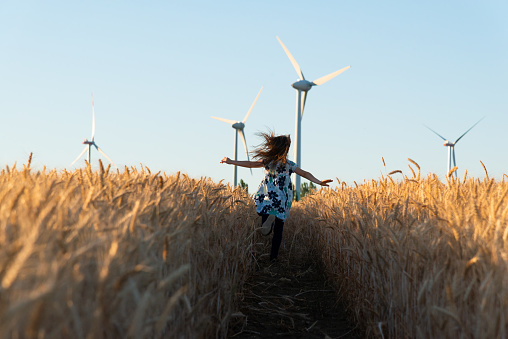 Girl Is Running The Way To Wind Energy Stock Photo - Download Image Now