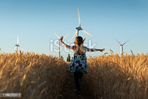 Girl is running the way to wind energy
