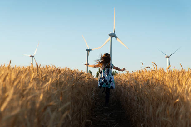 Girl is running the way to wind energy stock photo