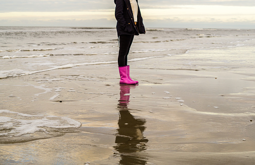 Girl is running with rubber boots at the beach