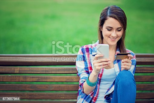 Girl is shopping online on the bench in park