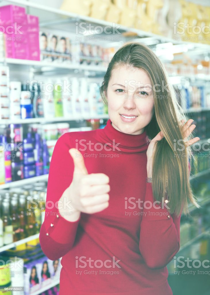 Girl is showing her hair and satisfied in the hair care shop royalty-free stock photo