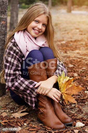 istock Girl is sitting in autumn park with maple leaves 492119004