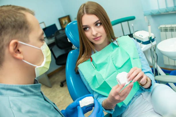 A girl is sitting in the dental chair and looking at a man doctor who is talking to her. dental clinic A beautiful girl is sitting in the dental chair and looking at a man doctor who is talking to her. dental clinic tranquilizing stock pictures, royalty-free photos & images