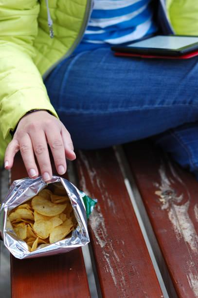 menina é sentado em um banco e comer batatas fritas - junk food - fotografias e filmes do acervo