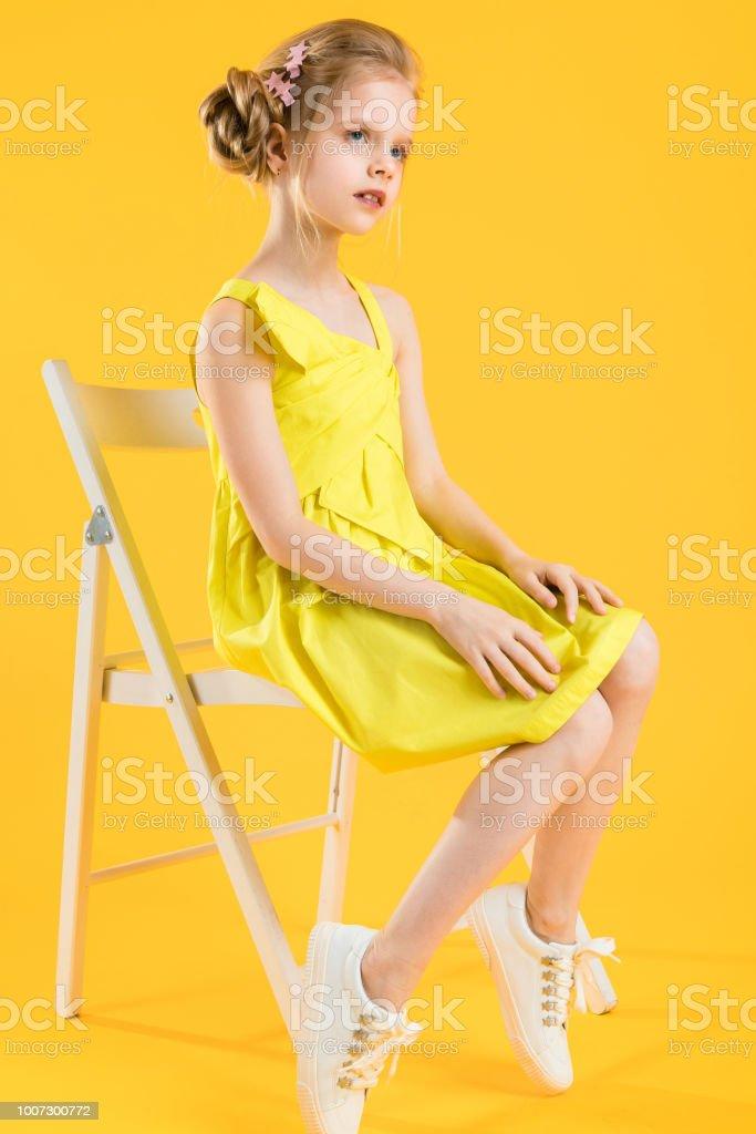 Eine Mädchen Sitzt Auf Einem Weißen Stuhl Auf Einem Gelben